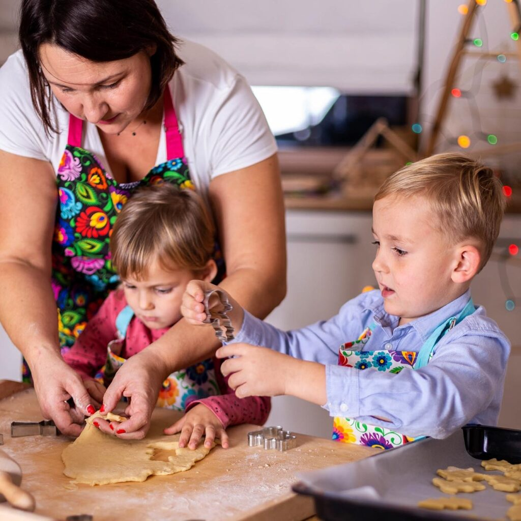 Dzieci i mama przygotowujący w kuchni ciasteczka amoniaczki