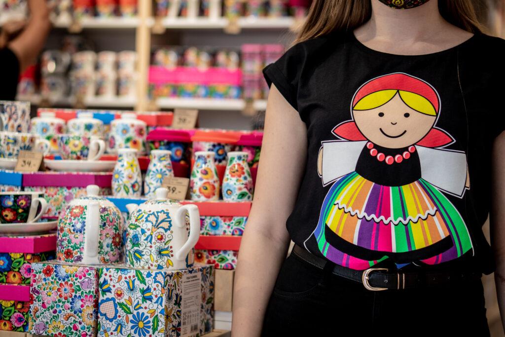 Dziewczyna w koszulce z Łowiczanką na tle sklepu Folkstar przy ulicy Grodzkiej w Krakowie