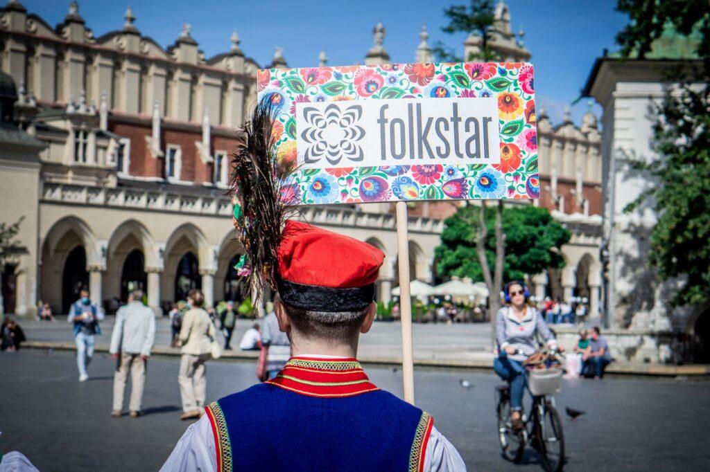 Mężczyzna w stroju ludowym krakowskim stojący przed sukiennicami z reklamą sklepu Folkstar w którym kupisz pamiątki z Krakowa